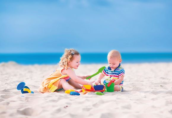 Toddler and baby playing on beach